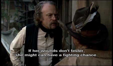 "Brad Dourif acting as Dr Amos Cochran in Deadwood. He says: ""If her wounds don't fester, she might can have a fighting chance."" He is wearing oval glasses low on his nose, and a black waistcoat over a white shirt. His hair is shoulder-length and greasy. He's talking to someone facing away from us wearing a hat with several feathers in it."