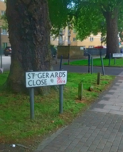 A street and broad verge on which stands a sign saying