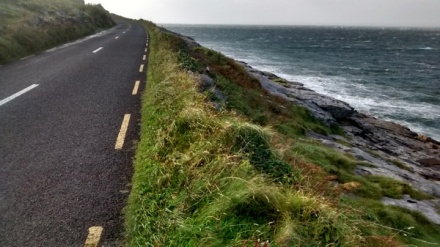 The coast road in north County Clare, Ireland, with the left-curving road overlooking a dark grey choppy sea, a thin sloping verge of rough grass and rock between them