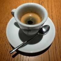 A half-full (or half-empty) cup of espresso on a saucer with a spoon