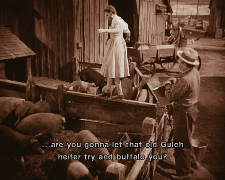 "This still image from the film is in sepia monochrome and shows Dorothy balancing as she walks along a fence abutting the pigsty on her farm. Various animals and farm tools and vehicles clutter the scene, and a large barn or house forms the backdrop. Behind Dorothy, on the right of the right of the image, Zeke stands with a bucket and says, ""...are you gonna let that old Gulch heifer try and buffalo you?"""