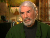 Gregory Peck, with grey hair and beard, wearing a green cardigan and dark polo-neck, sits indoors and talks about Cape Fear. Image from the making-of documentary on the Cape Fear DVD.