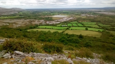 Photo of the Clare landscape, with hills in the distance, green fields and hedgerows and mixed forest in the middle-ground, and patches of granite in the foreground, at the edge of Mullaghmore. The sky is bright and cloudy.