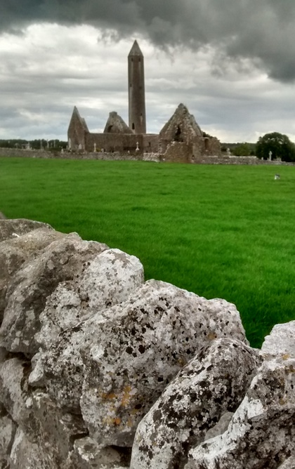 Foreground shows a roughly built stone wall, angled right; behind it is a lush green field. At the far end of the field stand the ruins of Kilmacduagh monastery and its round tower, looking imposing under dark-grey rainclouds