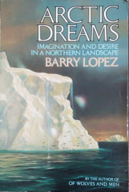Cover of Barry Lopez's book Arctic Dreams: Imagination and Desire in a Northern Landscape. The title is in large capital letters on the top right. The illustration encompassing the whole cover shows a large iceberg close up, with water dripping off it, and many seabirds flying near its base at the surface of the dark water. Another iceberg floats in the distance. The sky is muted grey, pink and blue.