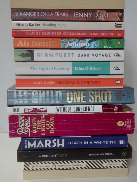 A vertical stack of books, with their spines facing the viewer and forming a found poem