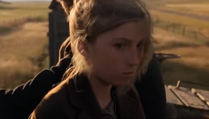 Image from the film 'Days of Heaven' showing Linda in closeup, with a serious, daydreaming expression. The vast flat surrounding fields are visible, out of focus, in the background.