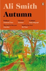 "Penguin UK book cover. The upper part is orange, with black and white text of the author's name, book title, and short blurbs from newspapers. Below this, on the bottom half and a little more, is a painting by David Hockney, ""Early November Tunnel"". It shows a sunlit path into the distance, with thick grassy verges and trees overhead, their leaves browning and shedding. A ridge of grass runs down the middle of the path."