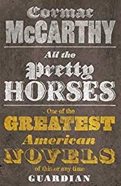 "Cover of Cormac McCarthy's book All the Pretty Horses. Background is brown, with large ornate white and yellow text, and no images. Under the author name and book title is a quote from the Guardian: ""One of the greatest American novels of this or any time"""