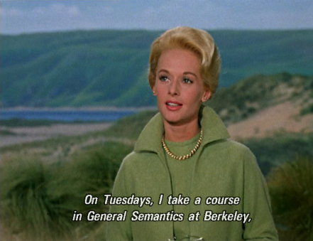 "Tippi Hedren stands among sand dunes, with a dark green hill and a thin slice of sea behind her. She wears a light green sweater, light green wool coat, and gold necklance, and speaks to someone off camera: ""On Tuesdays, I take a course in General Semantics at Berkeley,"""