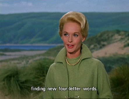 "Tippi Hedren stands among sand dunes, with a dark green hill and a thin slice of sea behind her. She wears a light green sweater, light green wool coat, and gold necklance, and speaks to someone off camera: ""finding new four-letter words."""