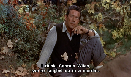 "John Forsythe sits on the ground, amidst dirt and leaves, wearing a light grey shirt with sleeves rolled up, black waistcoat, and dark grey trousers. He rests his left elbow on his raised left knee, looks up to his right, and says, ""I think, Captain Wiles, we're tangled up in a murder."""