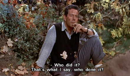 "John Forsythe sits on the ground, amidst dirt and leaves, wearing a light grey shirt with sleeves rolled up, black waistcoat, and dark grey trousers. He rests his left elbow on his raised left knee, looks ahead absent-mindedly, and says, ""Who did it?"""