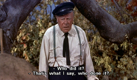 "Edmund Gwenn stands beneath a large tree branch, with leaves covering the space behind it. He wears a black sailing cap, a dark tie, a white shirt and suspenders, and says, in reply to Forsythe's ""Who did it?"", ""That's what I say, who done it?"""