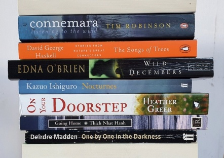 A stack of horizontal books, their spines facing out to form the poem quoted. The books are more or less centred, and the colours of their spines (orange, black, white and green, a few blues) creates a contrast with the blank white background.