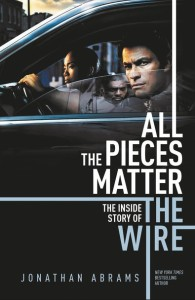 Book cover shows three characters from The Wire: McNulty and Kima Greggs (Sonja Sohn) are in a car, Greggs looking ahead and Mcnulty looking out his half-open window, his left hand on the steering wheel. Reflected in his window is Stringer Bell. Behind the car, blurred, is a Baltimore street and overcast sky. Below them all are the book title and author name in white and blue sans-serif caps.